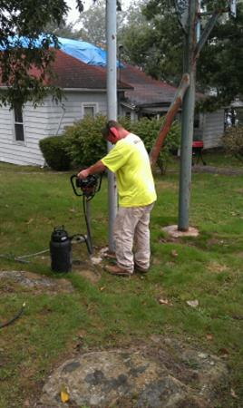 BHATE Engineering drilling for geotechnical sampling in backyard next to a pole.