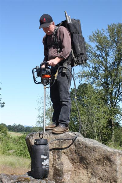 Neil Shaw drilling a boulder with the Shaw Backpack Drill